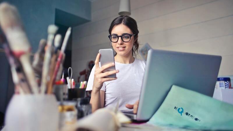 Mulher de óculos segurando smartphone em  frente ao notebook.