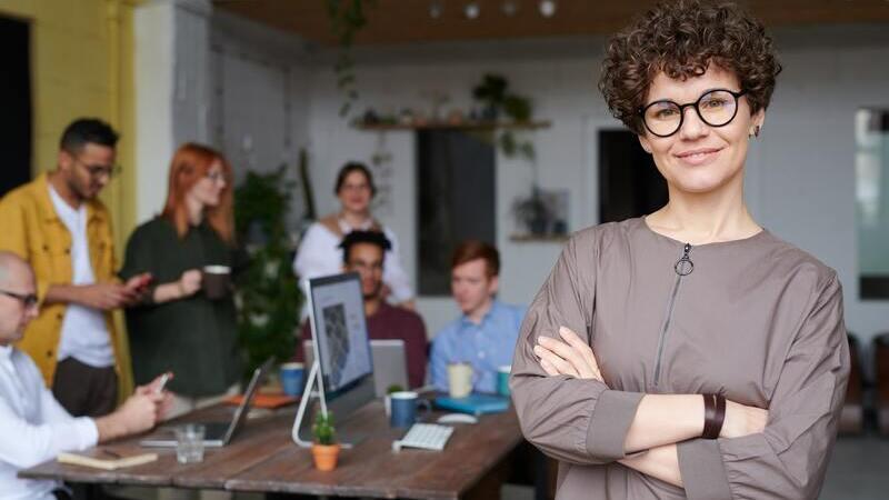 Em primeiro plano, uma mulher de braços cruzados e sorrindo. Atrás, pessoas trabalhando e conversando com computadores.