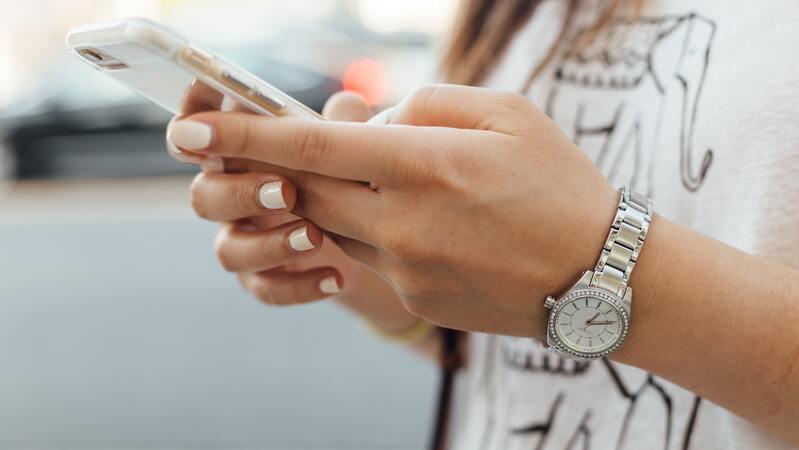 Mulher segurando smartphone com as mãos. No pulso há um relógio e ao fundo um carro passando.