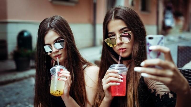 Duas mulheres de óculos escuros segurando copos com bebida colorida. Uma delas segura o celular para tirar uma foto