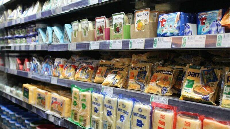 Gôndola de supermercado com queijos nas prateleiras.
