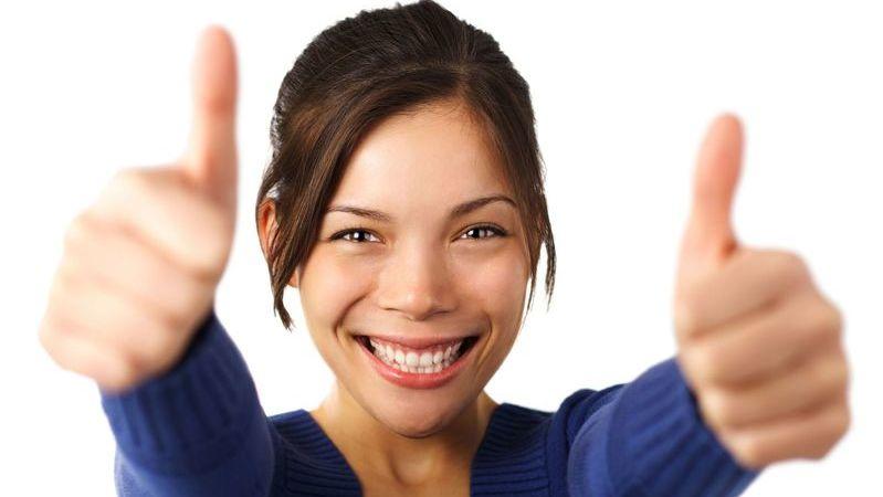 Uma mulher morena usando uma blusa azul, fazendo sinal de positivo com os dedos.