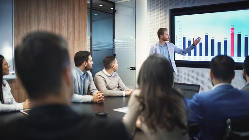 Há pessoas em uma sala de reunião e um homem de pé apresentando gráficos em um telão.