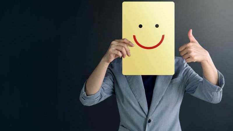 Pessoa fazendo sinal de positivo com a mão esquerda. Ela segura um cartaz com um rosto feliz desenhado na altura da cabeça.