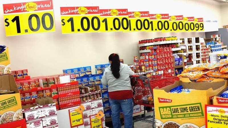 Mulher com carrinho de compras perto de produtos em oferta ao fundo de um supermercado.