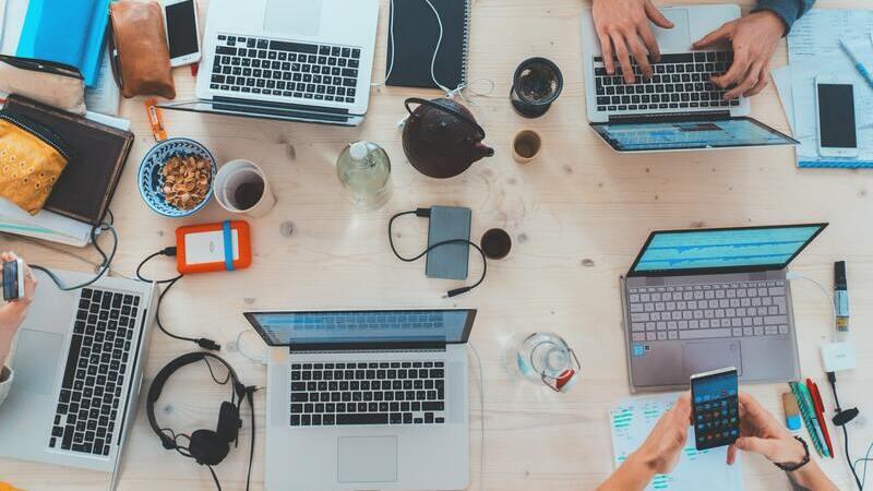 Há em uma mesa diversos notebooks, smartphones, comida e café. Há também 3 pessoas sentadas nessa mesa, mexendo nos objetos.