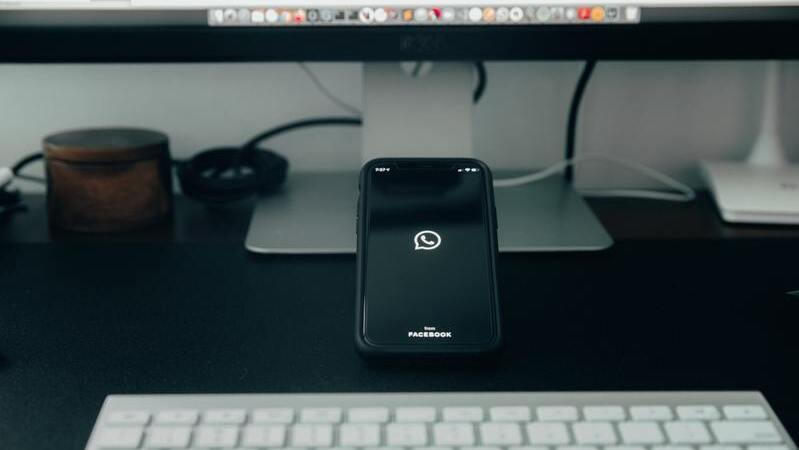 Smartphone com a logo do Whatsapp apoiado em monitor Imac.
