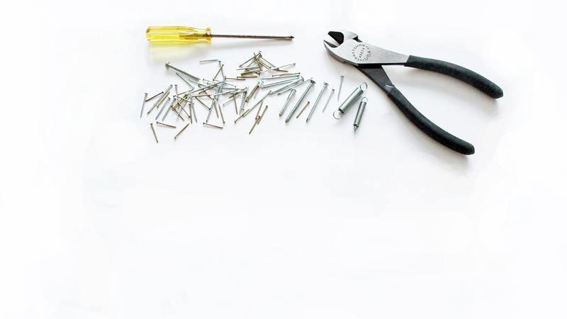 Sob uma superfície branca há um alicate de corte, chave phillips e vários pregos.