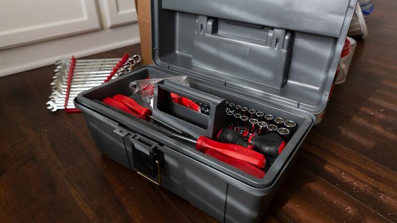Caixa de ferramentas sob piso de madeira. Dentro da caixa há ferramentas vermelhas de uso cotidiano