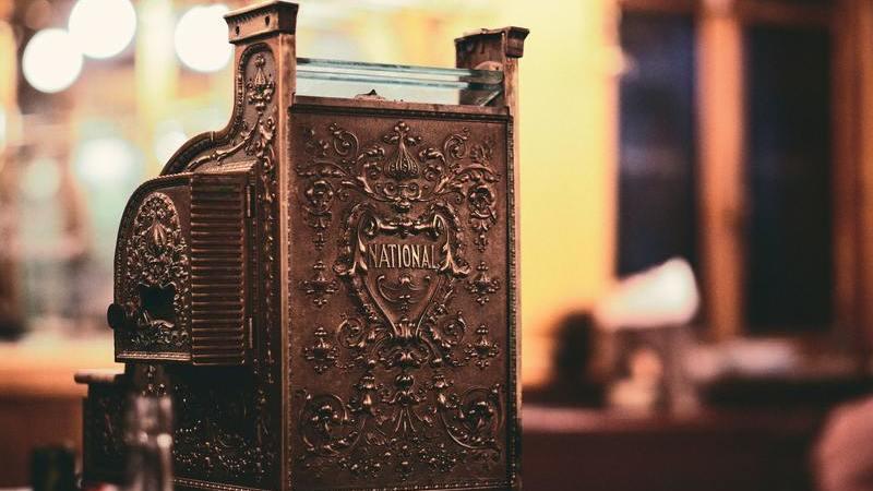 Em primeiro plano uma caixa registradora antiga, na cor de bronze. Ao fundo, uma loja desfocada