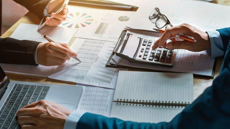 Braços de duas pessoas apoiados sobre uma mesa cheia de folhas com planilhas, gráficos, cadernos, calculadora e notebook.
