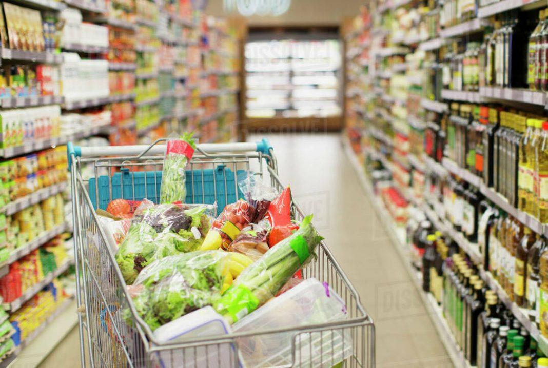 Carrinho de compras cheio de legumes e verduras parado em corredor vazio de supermercado.
