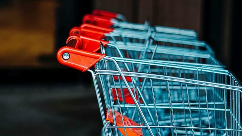 Carrinhos vermelhos de supermercado enfileirados em um local que já é noite