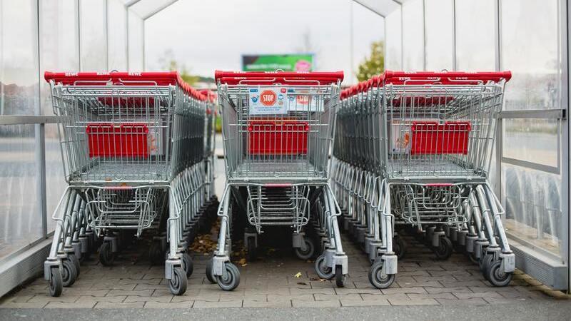 Carrinhos de supermercado de cor vermelha enfileirados em um estacionamento coberto.
