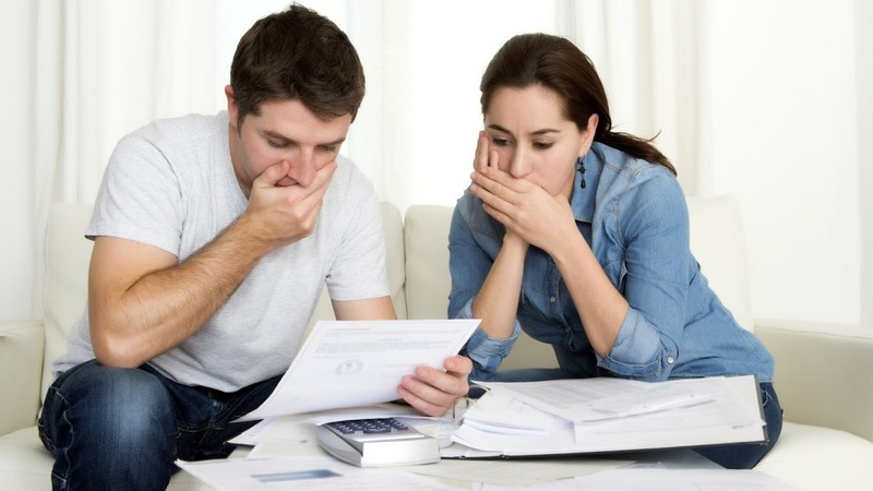 Um casal sentado no sofá cobre suas bocas com as mãos, mostrando semblante de preocupação ao lerem uma folha de papel.