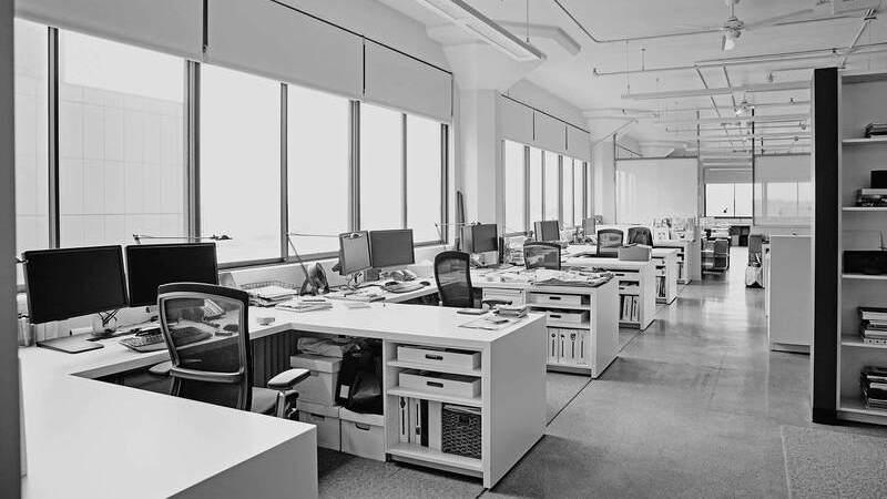 Imagem de um escritório amplo e vazio com estações de trabalho com mesa, cadeira e monitores nas cores preto e branco.