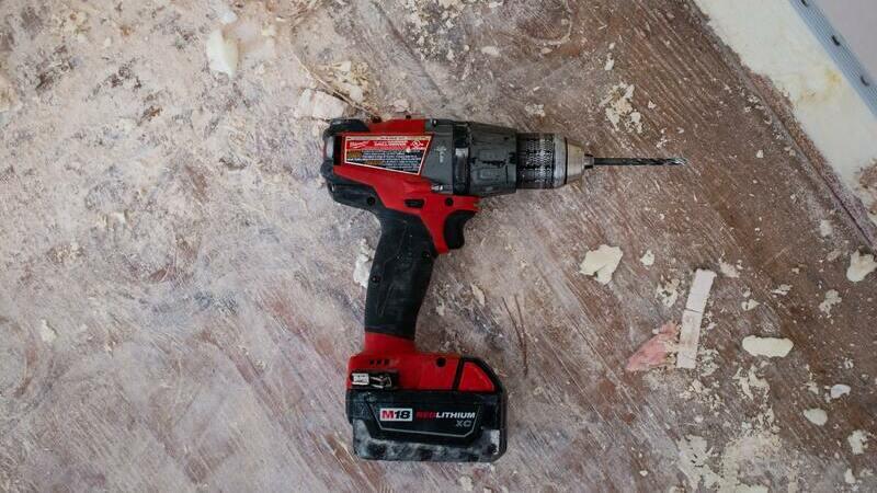 Furadeira vermelha e preta no chão de um local em reforma.