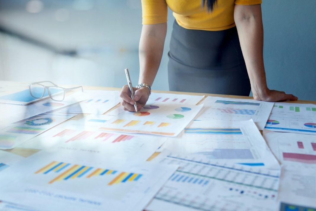 Mulher de blusa amarela e saia cinza segurando uma caneta sobre mesa cheia de papéis com gráficos coloridos.