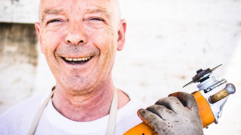 Homem sorrindo e segurando esmerilhadeira amarela com a mão direita coberta com luva de proteção