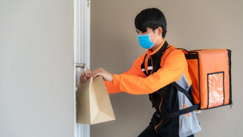 Homem de máscara de proteção segurando sacola de mercadorias. Ele coloca o produto pendurado na porta do cliente.