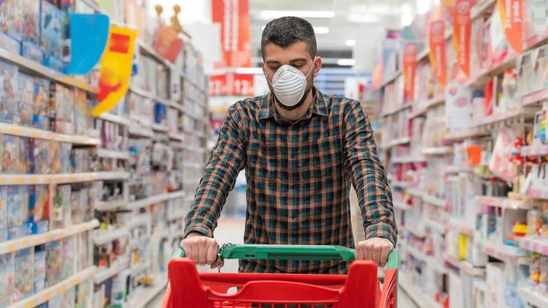 Homem usando máscara de proteção e empurrando carrinho de compras em corredor de uma loja.