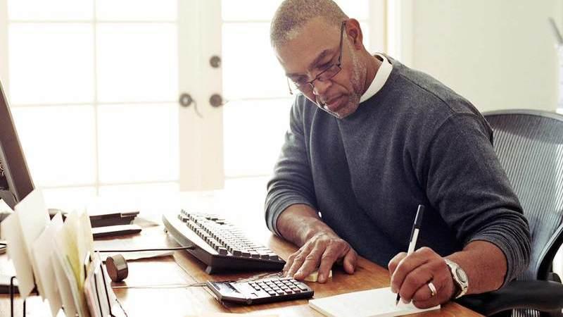 Homem de óculos sentado em escrivaninha escrevendo em um bloco de papel, próximo de uma calculadora e computador.