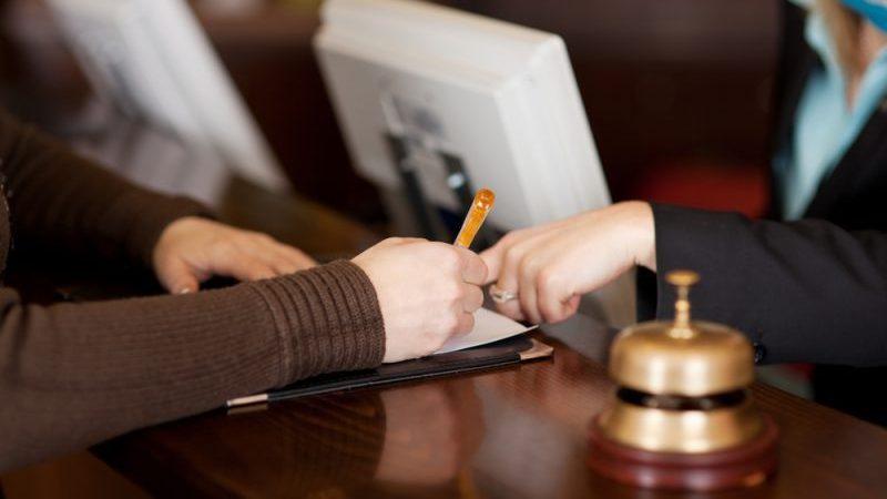 Pessoa assinando um papel no balcão de hotel ao lado da campainha, enquanto outra pessoa aponta o dedo em um ponto do papel