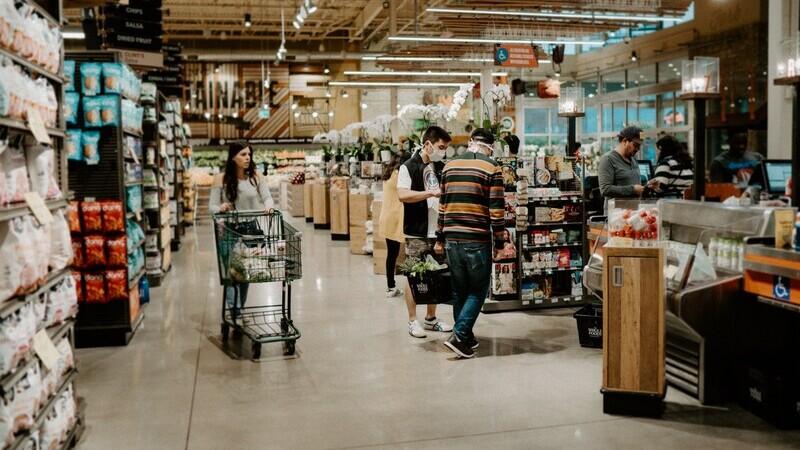 mulher empurrando carrinho de compras próxima de dois homens usando máscara segurando cesta de compras próximos do caixa do supermercado