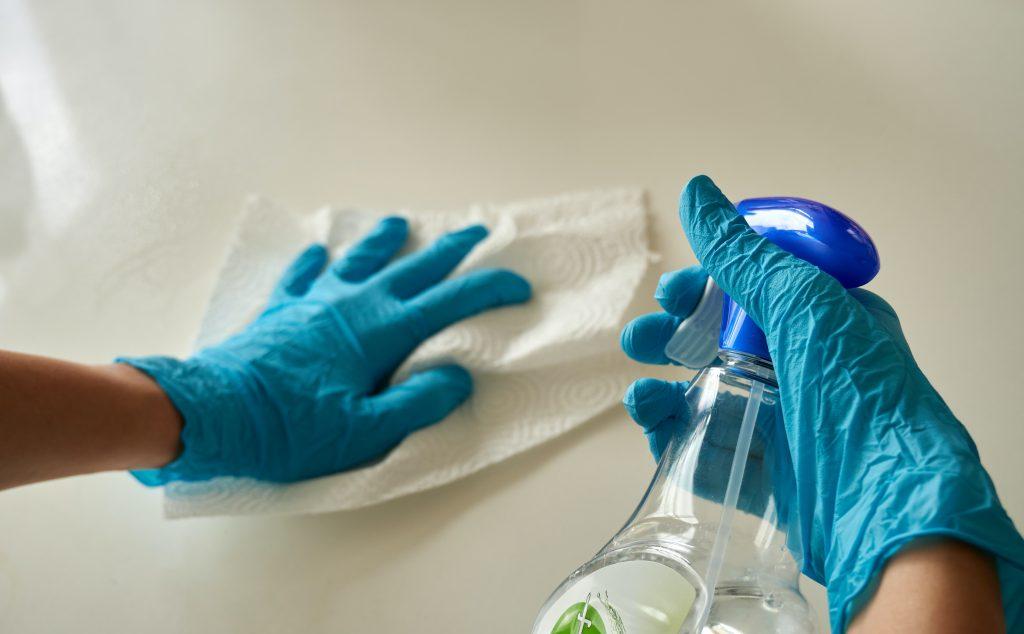 Mãos com luvas de borracha de cor azul limpando superfície branca. O produto de limpeza é usado em spray com um papel toalha.