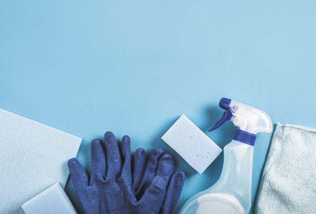 Luvas, panos, buchas e produtos de limpeza em superfície azul.