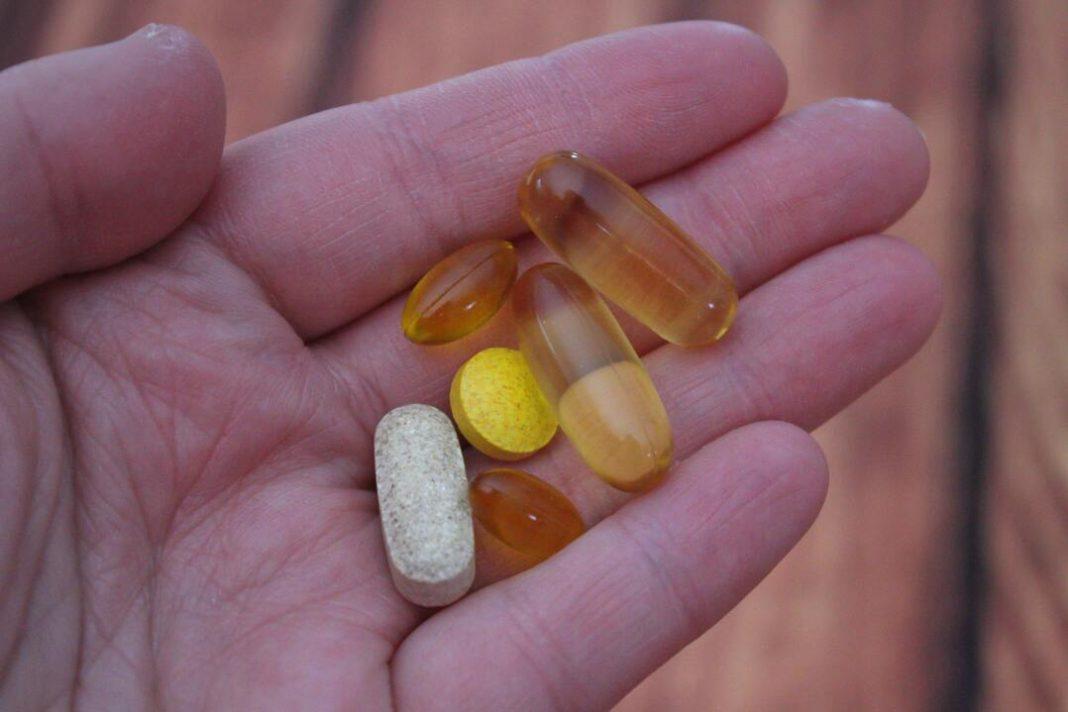 Close na palma da mão de uma pessoa segurando diferentes cápsulas e comprimidos de vitaminas.