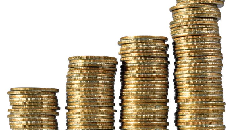 Quatro pilhas de moedas douradas organizadas em ordem crescente.