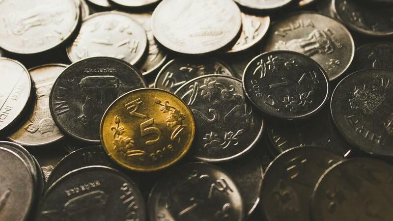 Várias moedas prateadas com uma moeda dourada por cima, em destaque