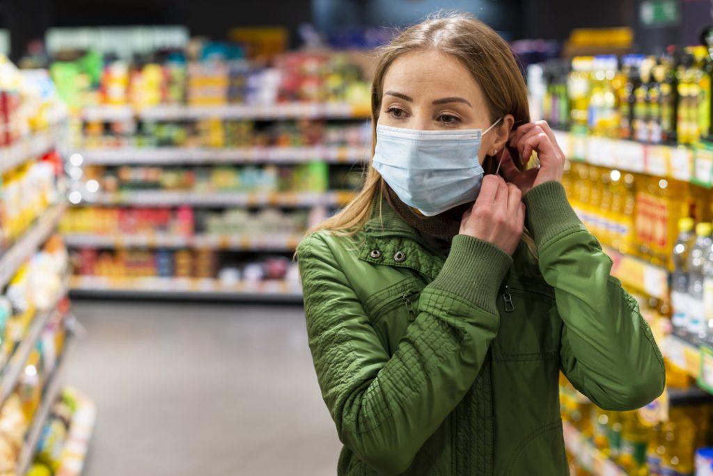 Mulher usando máscara de proteção no corredor de um supermercado.