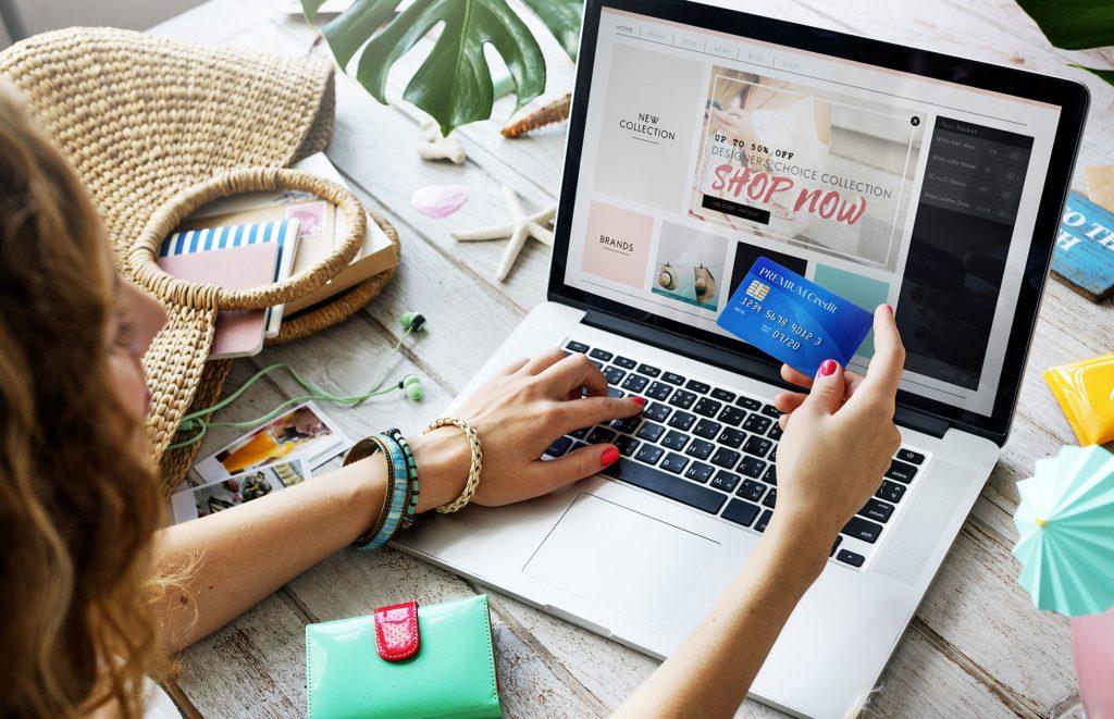 Uma mulher segura um cartão de crédito em frente a um notebook, que tem um site de loja virtual aberto.