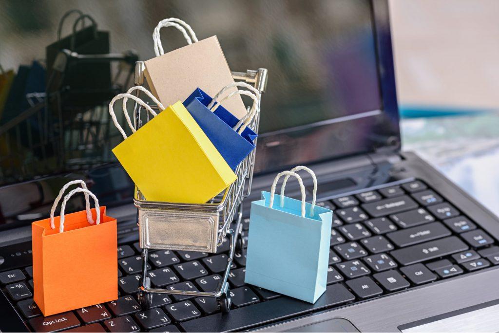 Carrinho de compras e sacolas de compra em miniatura sobre teclado de notebook aberto.