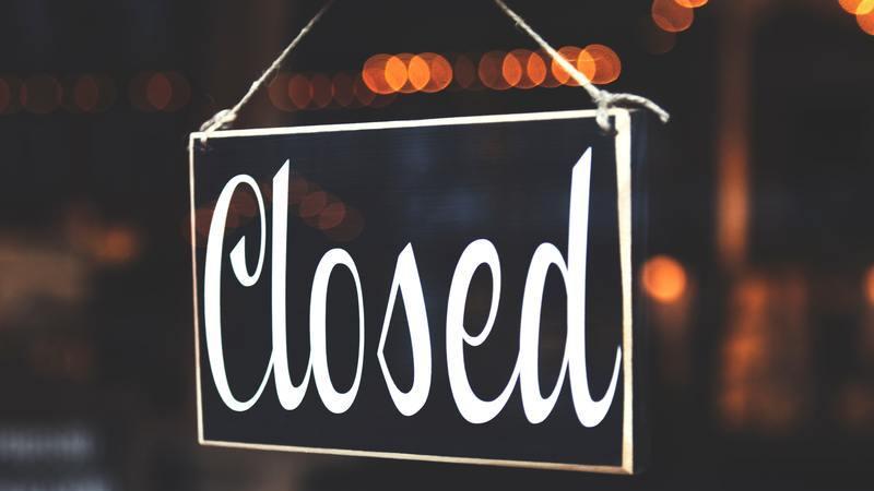 """Uma placa com a palavra """"closed"""" - que significa fechado - pendurada em uma porta de vidro."""
