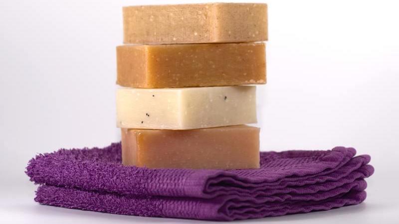 Quatro barras de sabonete sobre uma toalha roxa dobrada.