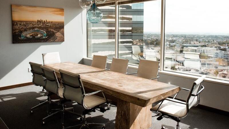 Imagem de uma sala de reuniões vazia, com oito cadeiras ao redor da mesa, quadro na parede e vista para prédios de uma cidade