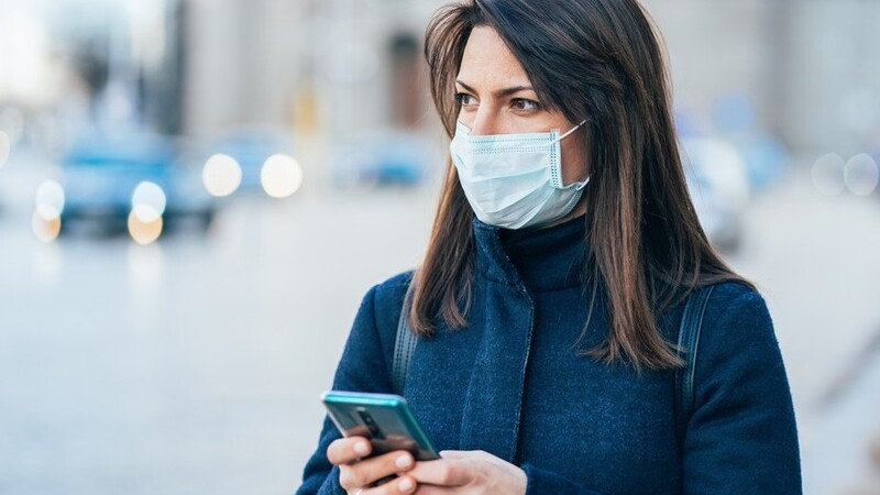 Mulher usando casaco e máscara de proteção e segurando um smartphone. Ao fundo cenas do trânsito da cidade desfocada.