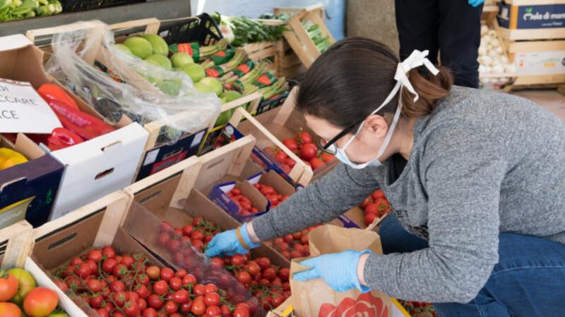 Mulher usando máscara de proteção e luvas nas mãos. Ela está pegando vegetais e legumes em um sacolão.