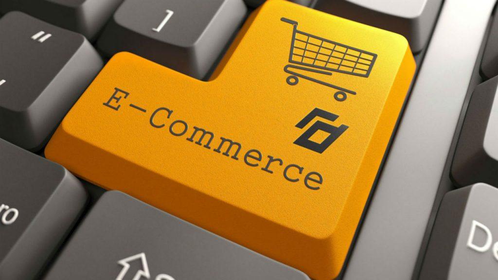 A imagem apresenta em destaque a tecla enter alaranjada escrito E-COMMERCE, além de uma ilustração de carrinho de compras