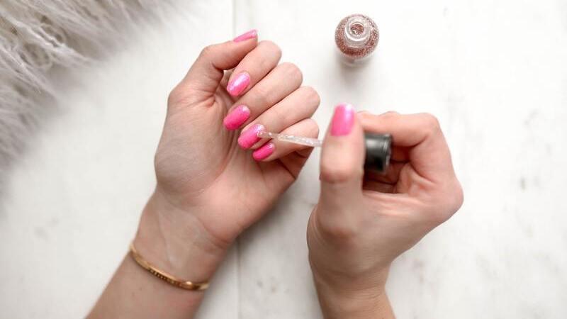 Mão feminina com unhas pintadas de cor de rosa segurando pincel de esmalte sobre a unha.