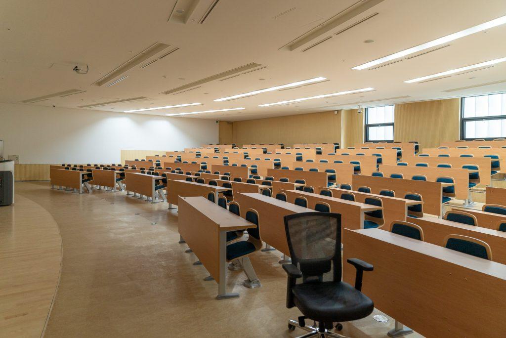 Auditório para palestras bem iluminado, com cadeiras e mesas vazias.