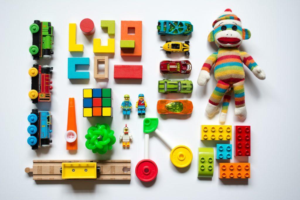 Brinquedos coloridos e enfileirados em superfície branca
