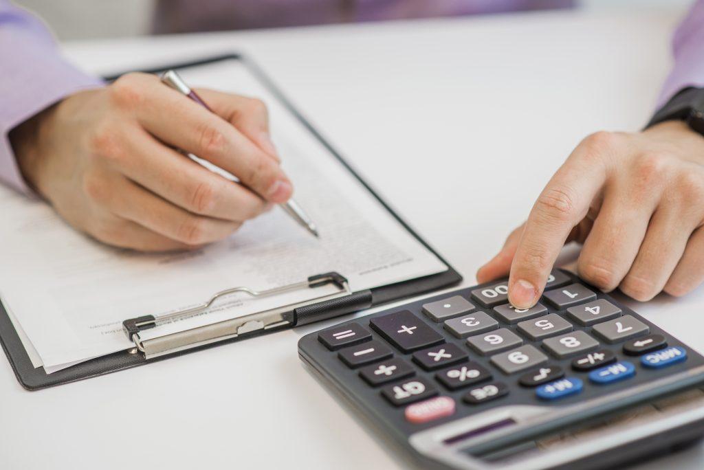 Pessoa usando calculadora e anotando em uma prancheta com uma caneta.
