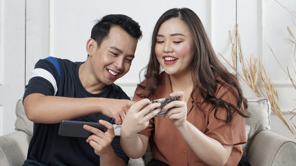 Homem e mulher, um casal, segurando smartphones e sorrindo. Eles estão sentados em um sofá.