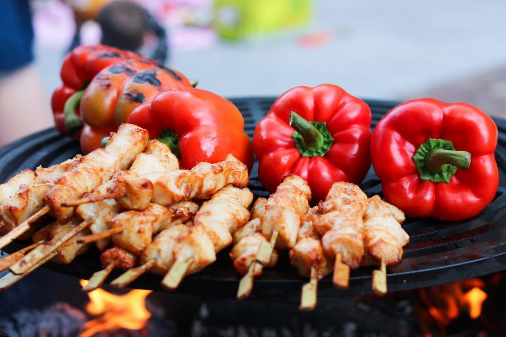 Churrasqueira com pimentões, tomates e espetos de frango na brasa