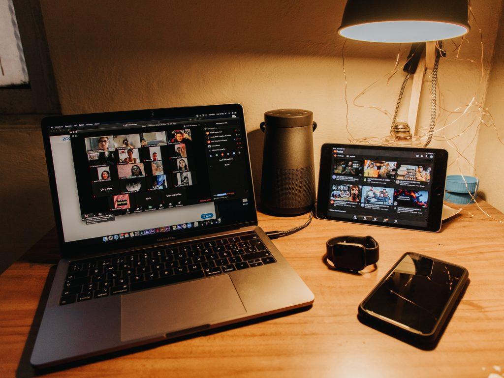 Notebook, tablet, relógio e smartphone sobre uma mesa. Há uma videochamada na tela de notebook e no tablet, alguns vídeos.