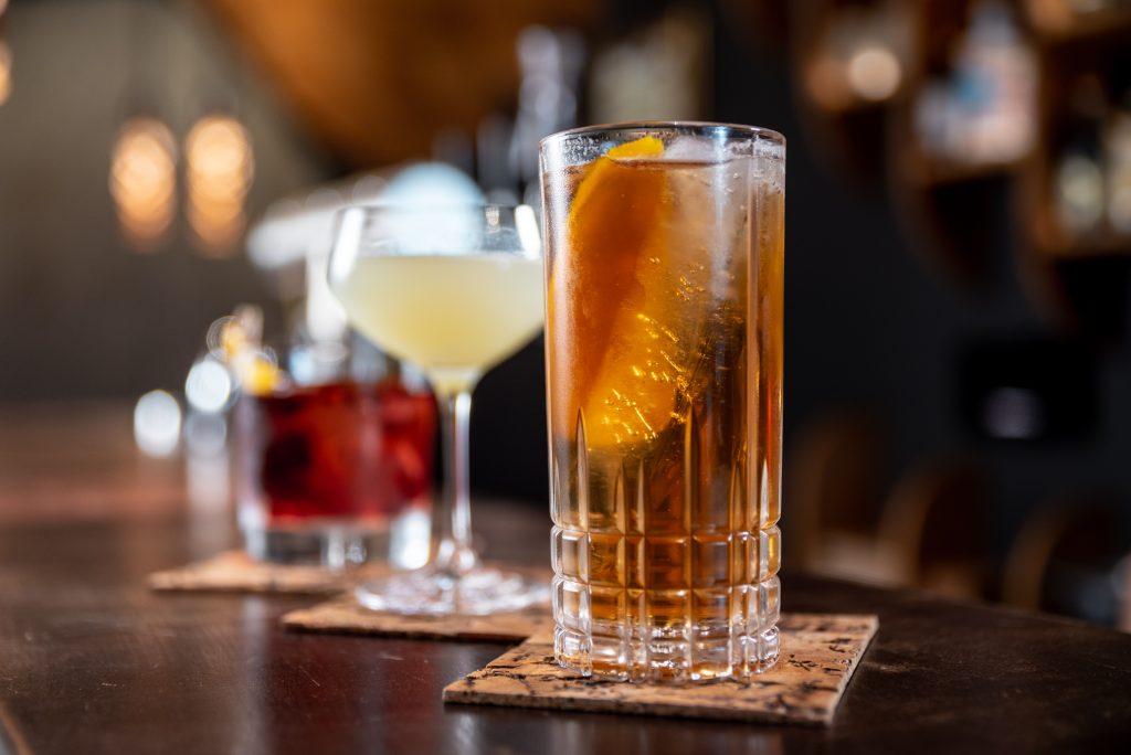 Ao fundo estrutura borrada do bar. Em primeiro plano, três drinks enfileirados no balcão.